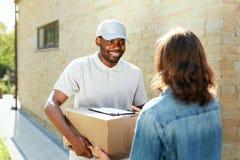 Druk levering uit Koerier die pakket levert stock fotografie