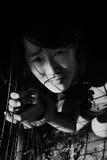 Druk vrouw met hand in in kooi wordt gebonden die stock foto