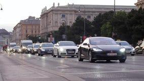 Drukke straat door dag, stroom van auto's op weg en fietsers op stoep voorbij gebouwen bij stad stock footage