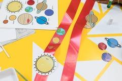 drukken van gekleurde te verwijderen planeten en lijm op een rood lint e royalty-vrije stock foto
