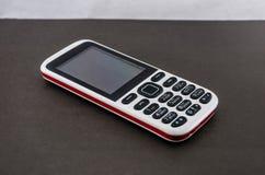Drukknop mobiele telefoon op een grijze achtergrond stock fotografie