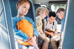drukte samen weinig schoolmeisjezitting alleen in schoolbus terwijl in haar klasgenoten die pret hebben stock foto