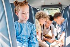 drukte weinig schoolmeisjezitting alleen in schoolbus terwijl in haar klasgenoten samen gebruikend smartphone royalty-vrije stock afbeelding