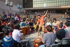 Drum circle at Kowloon Prominade in Hong Kong, China. HONG KONG, CHINA - 18 JAN 2015: Facilitator Channon Liu, directs tourists and visitors as they participate Stock Photography