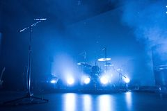 Drum kit and microphone on an empty stage. A kit of drums and a microphone on an empty stage in blue smoke before the concert royalty free stock image