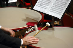 Drum-roll!. Close-up of timpanists hands using mallets to play timpani, showing hands, sticks, tuning-gauges and music Stock Photos