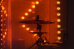 Drum set with cymbals in red stage lights. Live rock music photo background, rock drum set with cymbals in red stage lights. Close-up photo, soft selective focus royalty free stock photography