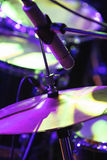 Drum set with microphone. Rock concert series: drum set with microphone, lit by purple and green Royalty Free Stock Images