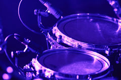 Drum set with microphones. Rock concert series: drum set with microphones, lit by purple and blue Royalty Free Stock Photo