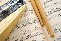Drum Sticks And Metronome On Music Score Royalty Free Stock Photo