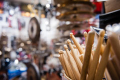 Drum sticks close up in drum store. Many drum sticks close up and out of focus  drum store showroom in background Royalty Free Stock Photography