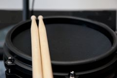 Drum sticks with electric snare. Black electronic drum with two wooden sticks resting with copy space to the e royalty free stock images