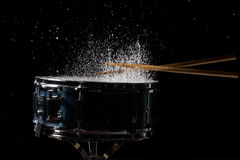 The drum sticks are hitting. On the snare drum with splash water in low light background stock photos