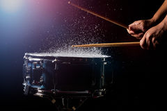 The drum sticks are hitting. On the snare drum with splash water in low light background royalty free stock photos