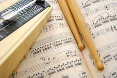 Drum sticks and metronome on music score Royalty Free Stock Photo