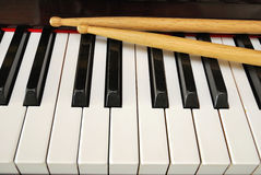 Drum sticks on piano keyboard Royalty Free Stock Photography