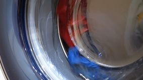 The Drum of the Washing Machine Rotates with Clothes. Washing clothes in the washing machine stock video