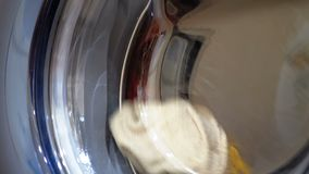 The Drum of the Washing Machine Rotates with Clothes. Washing clothes in the washing machine stock footage