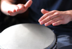 Drumer's hands. Medium sized drum on the laps of performer. Shallow depth of field used to make accent on one side of the drum. Artist's hands are moving fast royalty free stock images