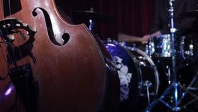 Drumm kit and contrabass jazz musical instruments. Musicians playing contrabass drums on stage. Artists play wooden. Double bass on stage dark background stock video footage