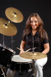 Drummer. Beautiful girl-drummer on the black background Royalty Free Stock Photos