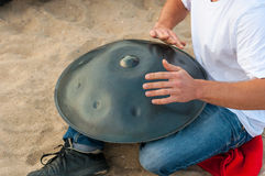 The drummer in action. guy sitting on the sand beach and playing handpan or hang. Hang is traditional ethnic drum Stock Photo