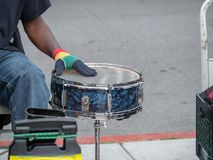 Drummer beats on steel drum on sidewalk in a street performance. Outside Stock Images
