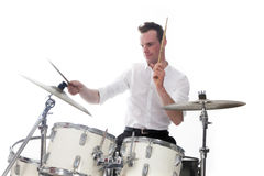 Drummer behind drum set wears white shirt and plays the drums Stock Photo