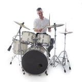 Drummer behind drum set wears white shirt and plays the drums Royalty Free Stock Images