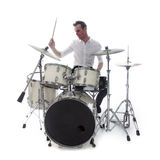 Drummer behind drum set wears white shirt and plays the drums Stock Photos
