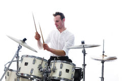 Drummer behind drum set wears white shirt and plays the drums Stock Image