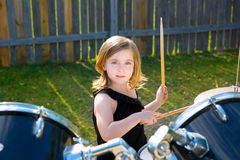 Drummer blond kid girl playing drums in tha backyard Stock Photography