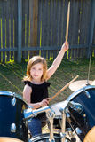 Drummer blond kid girl playing drums in tha backyard. Lawn royalty free stock images