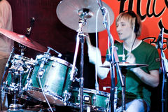 Drummer in blue light. Drummer in green t-shitr plaing music Royalty Free Stock Photography