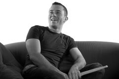 Drummer Boy. A drummer sitting relaxed on the couch, laughing royalty free stock images