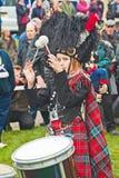 Drummer at Braemar Royal Gathering. Drummer in tartan cape  with drum sticks raised at Braemar Royal Gathering held on 1st September 2012 Royalty Free Stock Image