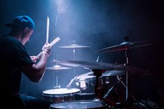 Young drummer at work. Drummer in a cap and headphones plays drums at a concert under blue light in a smoke royalty free stock photography