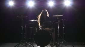 Drummer comes off at a rock concert. Black smoke background. Silhouette. Drummer comes off at a rock concert, plays energetic music and enjoys the event. Black stock video footage