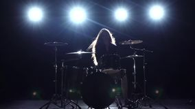 Drummer comes off at a rock concert. Black smoke background. Silhouette. Slow motion. Drummer comes off at a rock concert, plays energetic music and enjoys the stock video footage