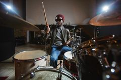 Drummer. Contemporary and popular African-american musician playing drums during repetition Royalty Free Stock Photos