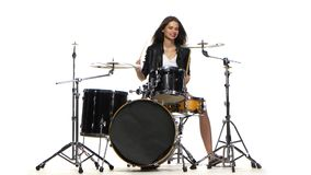 Drummer girl starts playing energetic music, she smiles. White background