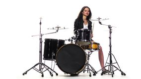 Drummer girl starts playing energetic music, she smiles. White background. Slow motion stock video