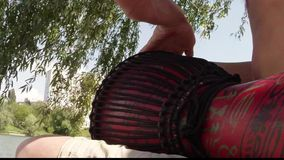 Drummer hands playing on a makeshift drum on a background of lake and building stock video