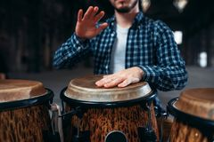 Drummer hands playing on wooden drum, closeup. Bongo, musical percussion instrument, ethnic music Royalty Free Stock Images