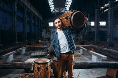 Drummer holds wooden drum on the shoulder. Young male drummer holds wooden drum on the shoulder, factory shop on background. Djembe, musical percussion Royalty Free Stock Photography