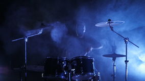 The drummer in mask plays the drum set on the stage. Shot in a slow motion. Music video punk, heavy metal or rock group. Concert rock band performing on stage stock video footage