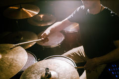 Drummer playing cymbals during concert. Drum set background, atmospheric stage lightning stock photography