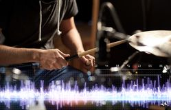 Drummer playing drum kit at sound recording studio. Music, people, musical instruments and technology concept - close up of musician with drumsticks playing drum Royalty Free Stock Photo