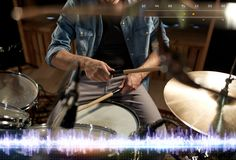 Drummer playing drum kit at sound recording studio. Music, people, musical instruments and technology concept - close up of musician with drumsticks playing drum Stock Photo
