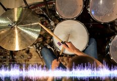 Drummer playing drum kit at sound recording studio. Music, people, musical instruments and technology concept - close up of musician with drumsticks playing drum Royalty Free Stock Image